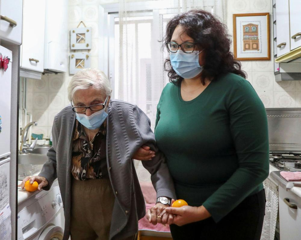 Her caregiver Olga Arauz wears a protective mask when she is in Martin's home.