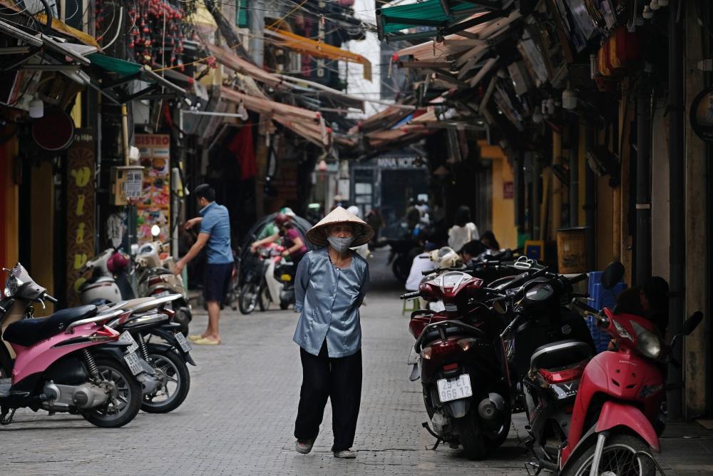 A woman wearing face mask walks in a street in Hanoi, Vietnam, on 27 April 2021.
