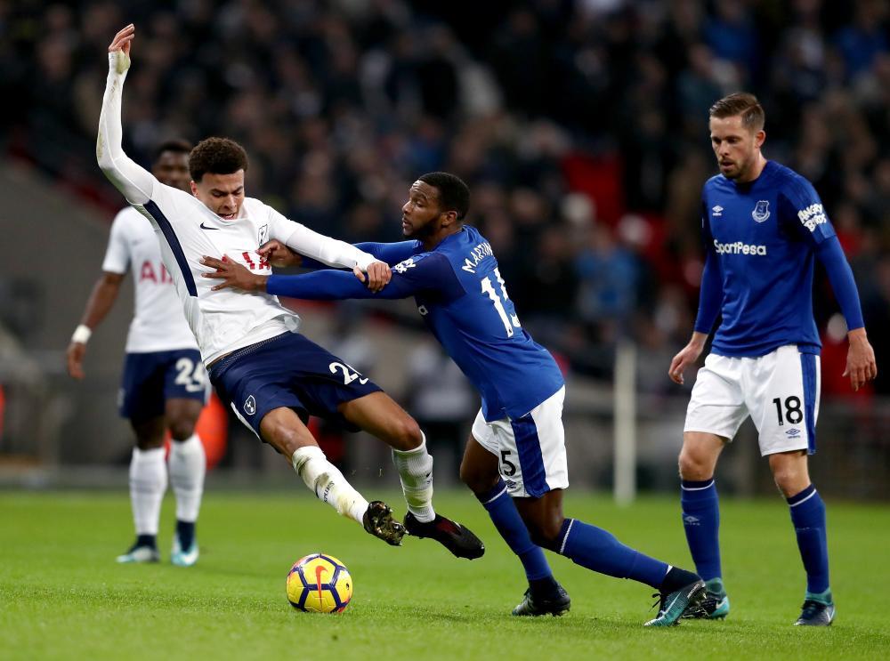 Dele Alli of Tottenham Hotspur tussles with Cuco Martina of Everton.