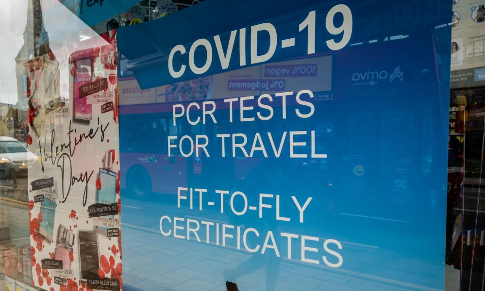 A poster in the window of a pharmacy offering commercial Covid-19 PCR test for travel