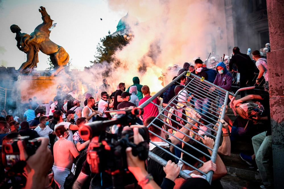Protesters clash with police in front of Serbia's national assembly building in Belgrade.