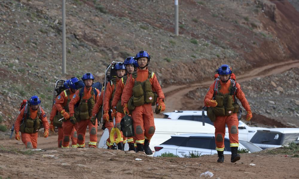 Rescuers walk into the accident site where 21 ultrarunners died in north-west China's Gansu province.