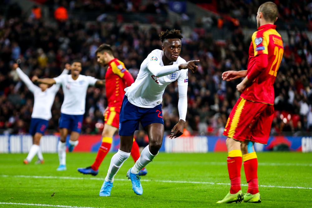 Tammy Abraham of England celebrates scoring a goal to make it 7-0, pointing to Jadon Sancho of England who provided the assist.