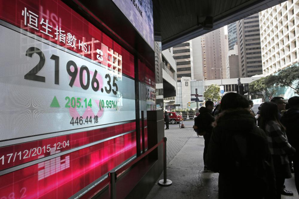 Passersby stand in front of an electronic board showing Hong Kong share index outside a local bank in Hong Kong, Thursday, Dec. 17, 2015. Global stocks posted broad gains Thursday after the Federal Reserve ended protracted uncertainty by raising interest rates for the first time in nearly a decade and signaling that further increases will be gradual. (AP Photo/Vincent Yu)