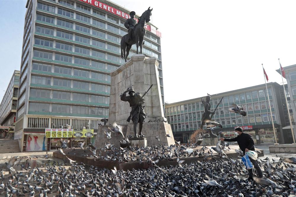 A man feeds the piegeons on the empty Ulus Square