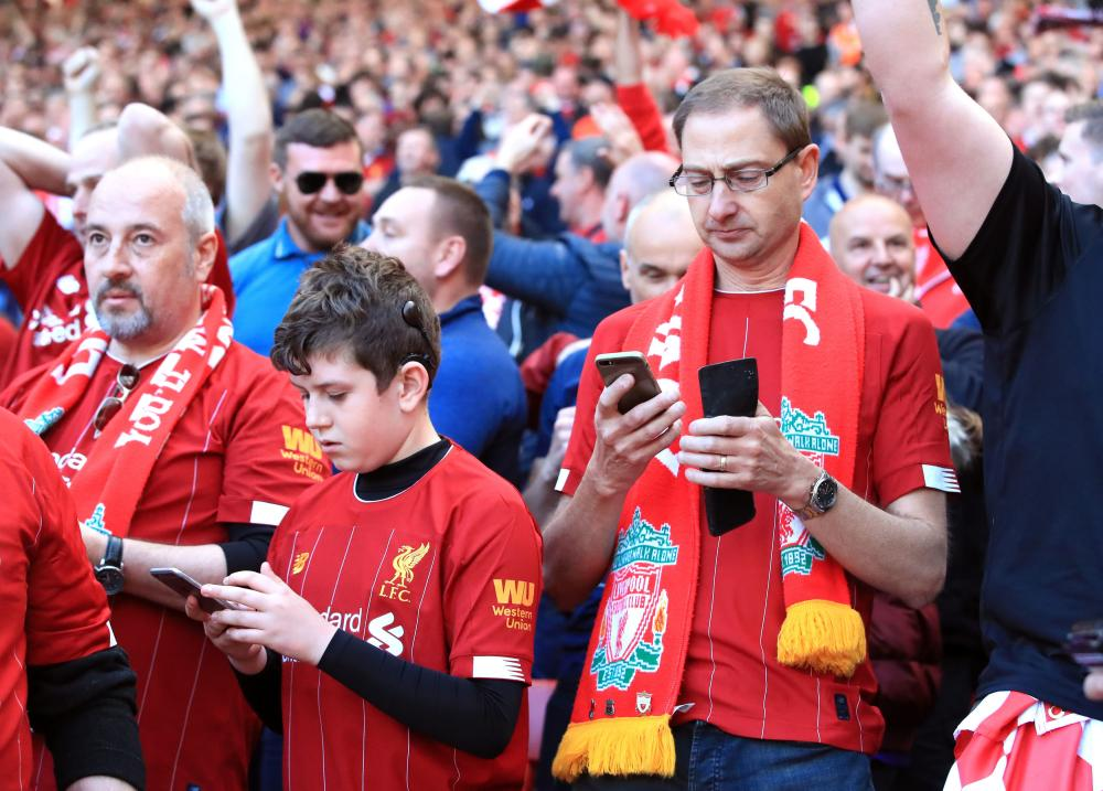 Liverpool fans check their mobile phones for updates.