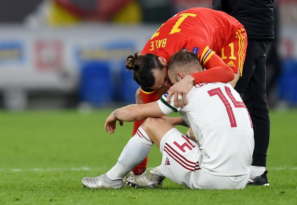 Gareth Bale comforts a dejected Gergo Lovrencsics.
