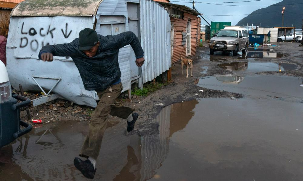 A man leaps over pools of water along a flooded road in the Masiphumelele informal settlement in Cape Town, South Africa, 11 June 2020.