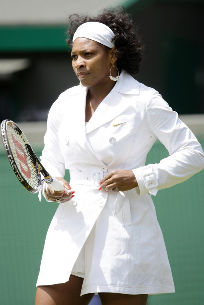 Serena Williams warms up for her match against Kaia Kanepi in 2008, in a white trench coat.