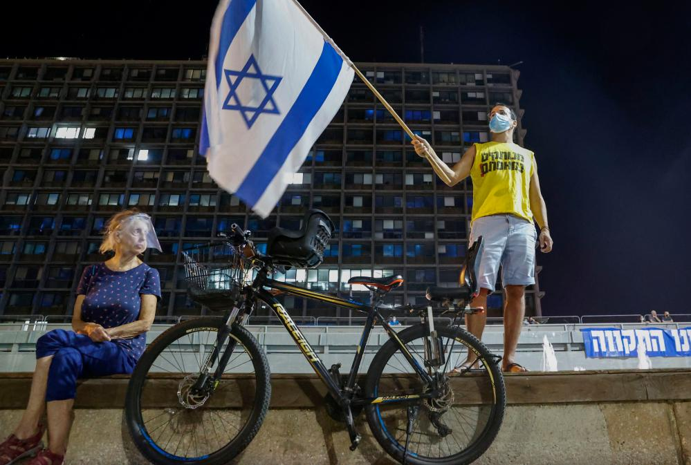 Israeli protesters, wearing protective gear due to the coronavirus pandemic, take part in a demonstration against prime minister Benjamin Netanyahu in the coastal city of Tel Aviv.