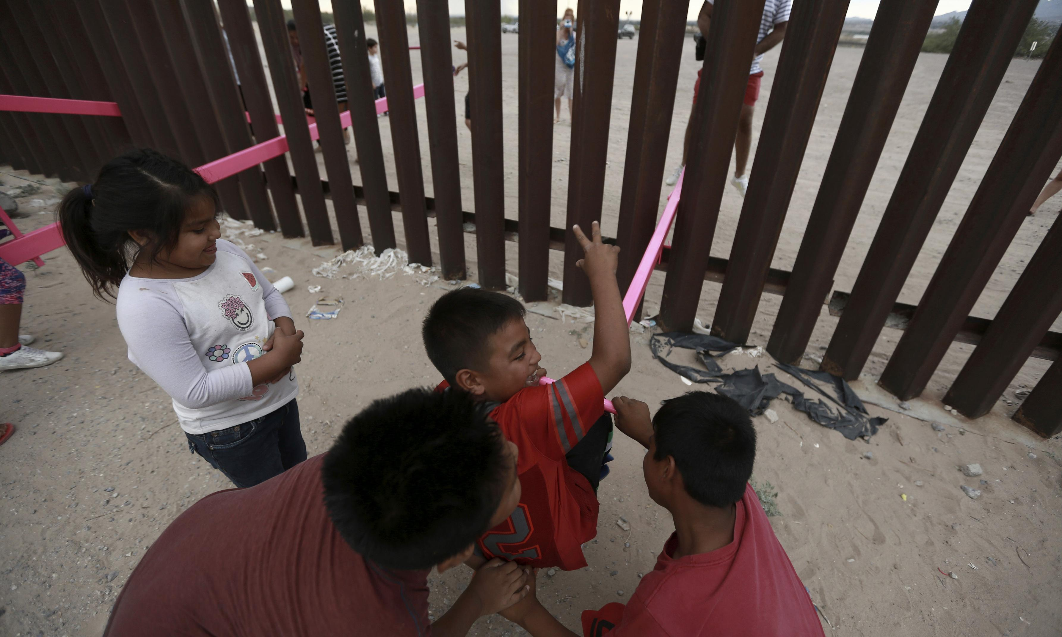 Pink seesaws reach across the divide at US-Mexico border