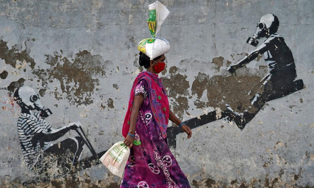 A woman wearing a protective face mask walks past a graffiti, after authorities eased lockdown restrictions, in Mumbai, India