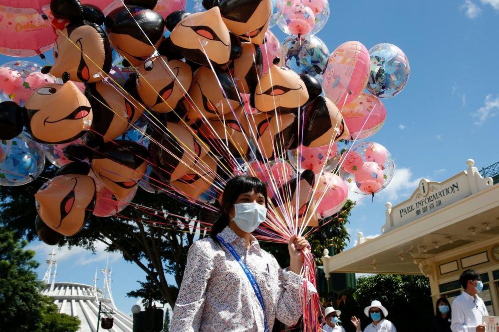 An employee holding balloons at the Disneyland theme park in Hong Kong after it reopened in June following its first shutdown due to the coronavirus.