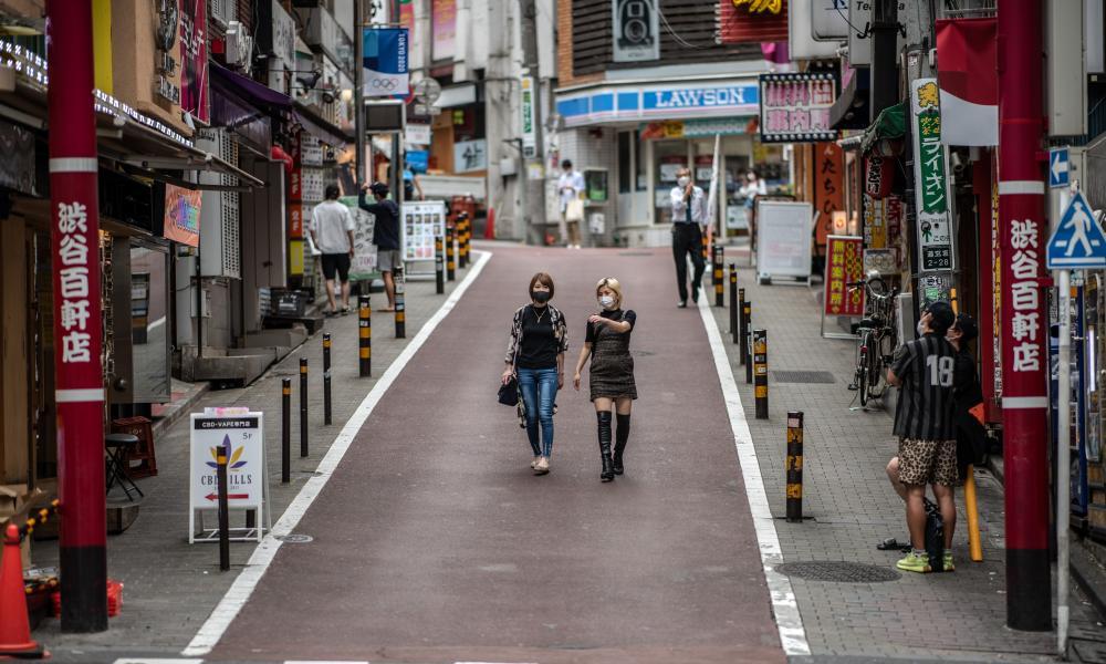 Women wearing face masks walk through Shibuya in Tokyo, Japan. A