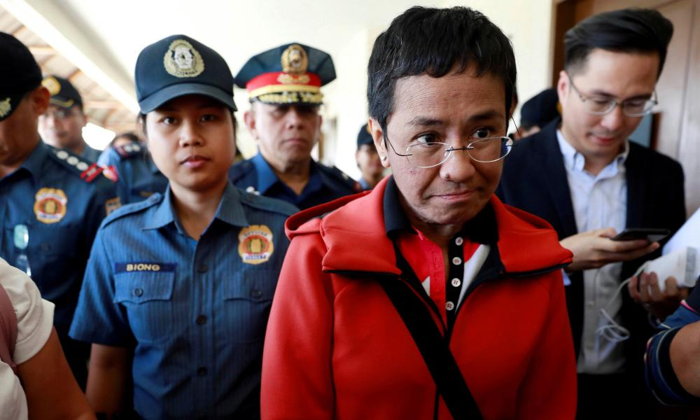 'In the face of multiple threats, criminal charges and two arrests, Maria Ressa has continued to speak out.' Maria Ressa is escorted by police after posting bail.