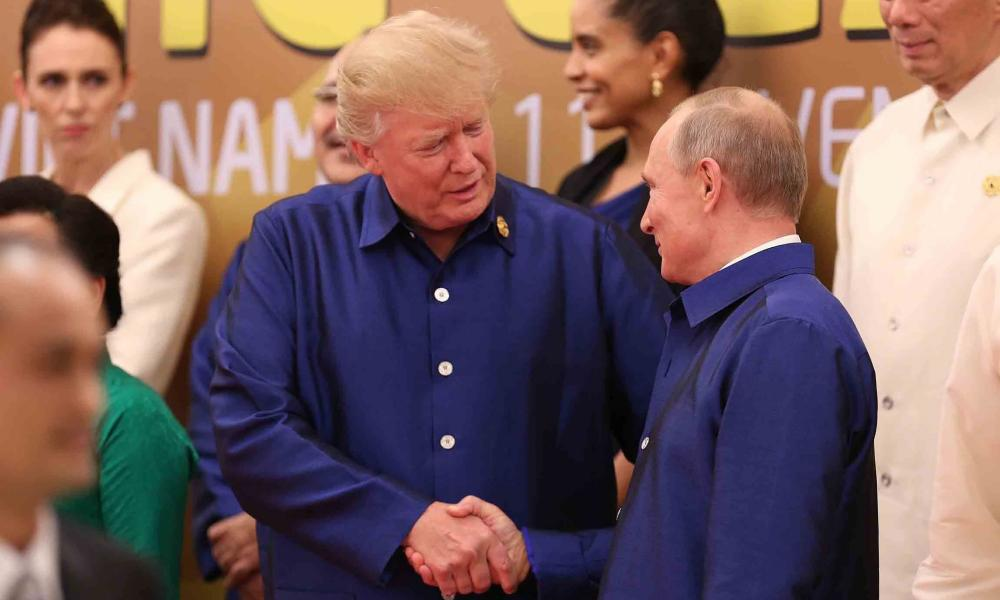Donald Trump shakes hands with Vladimir Putin as they pose for a group photo ahead of the Apec summit gala dinner.