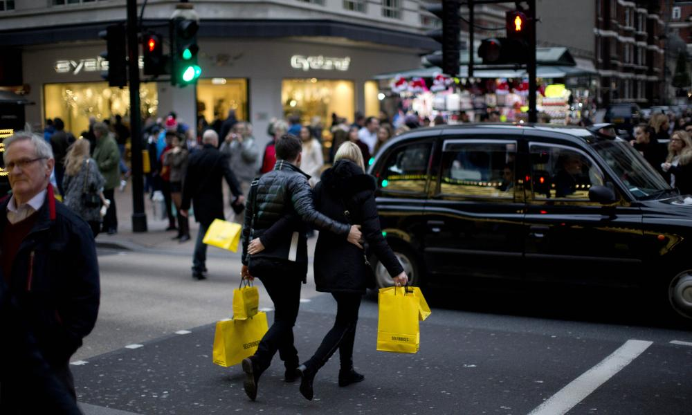 People carrying shopping bags cross Oxford Street in London, Tuesday, Dec. 22, 2015. There are two shopping days remaining until Christmas. (AP Photo/Matt Dunham)