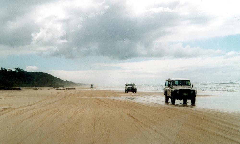"4WD vehicles speed down Fraser Island's ""freeway"" - 75-Mile Beach."