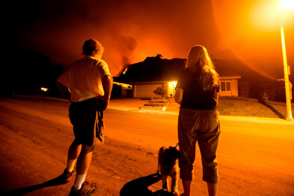 People watch as the Bobcat Fire burns on hillsides behind homes in Monrovia, California on September 15, 2020.