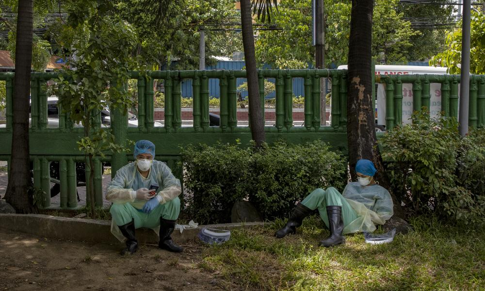 Medical personnel in protective take a break from treating patients at a parking lot converted into a Covid-19 isolation facility on 30 April 2020 in Quezon city, Metro Manila, Philippines.