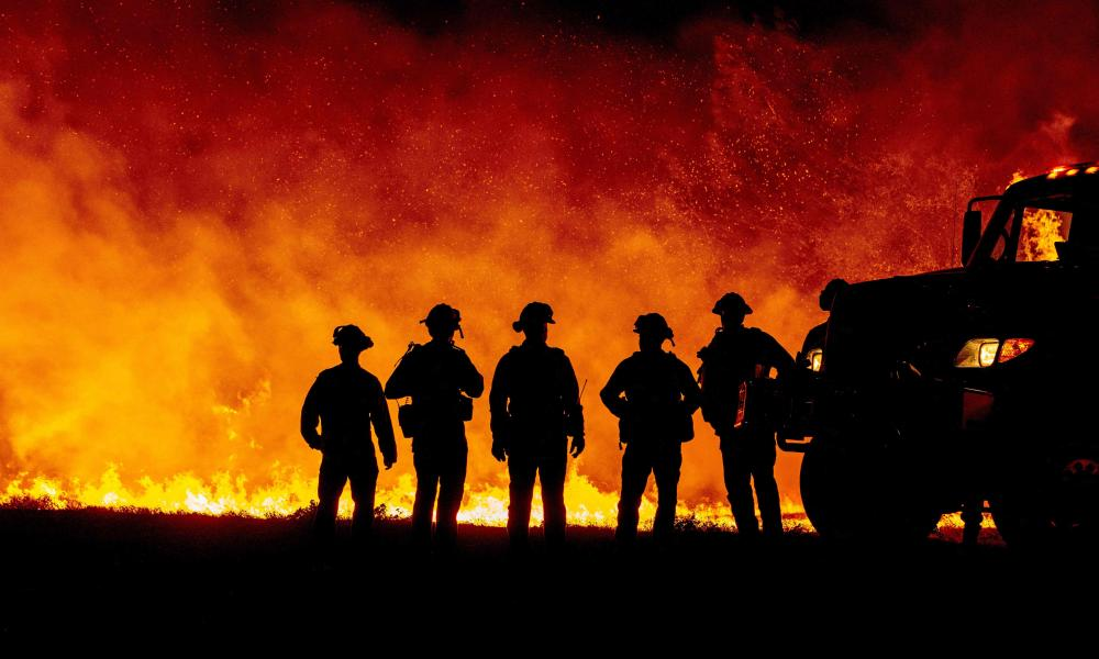 Butte County firefighters watch as flames quickly spread across a road at the Bear fire in Oroville, California.