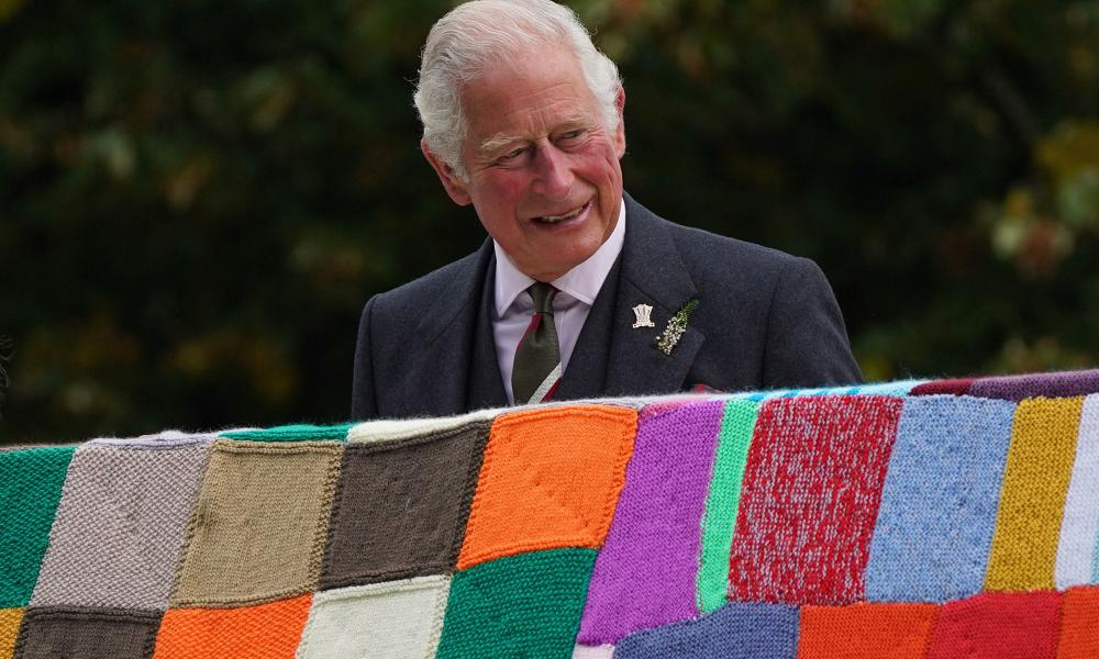 Prince Charles holds up a giant blanket of multicoloured knitted squares