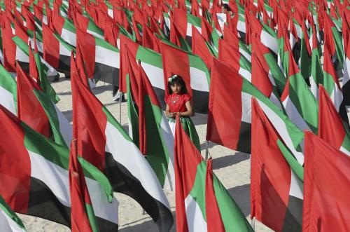 An Emirati girl walks inside the 'Flags Garden '