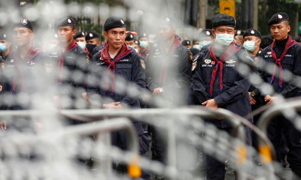 Police officers stand in lines as they close a road near Ratchaprasong junction in Bangkok