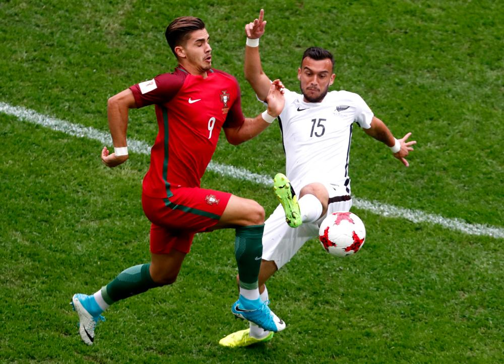 Clayton Lewis of New Zealand, right,and Andre Silva of Portugal tussle for the ball.