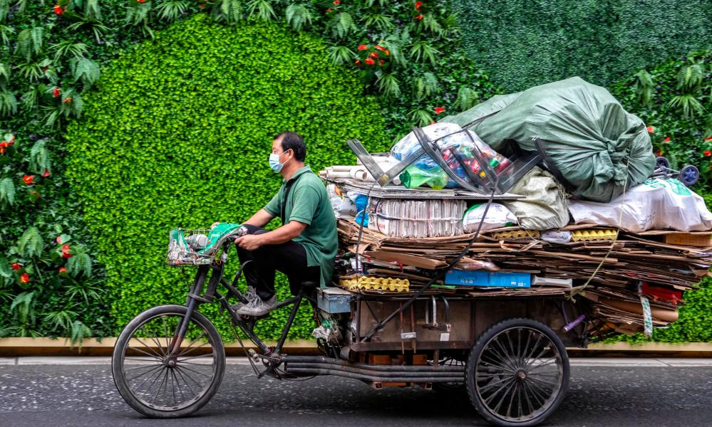 A man rides a tricycle with the garbage in Shanghai, China, 13 July 2020.