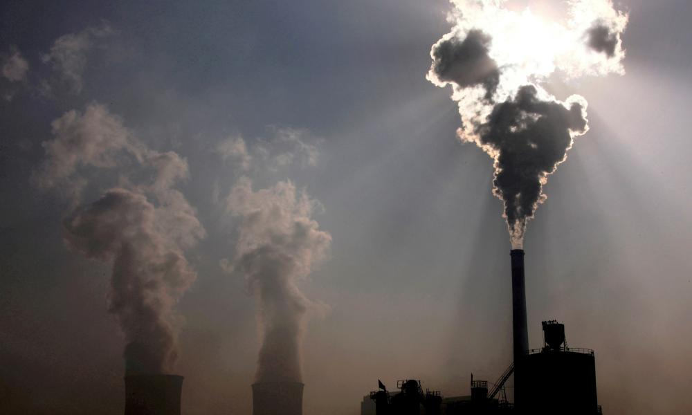 coal-burning power plant can be seen behind a factory in the city of Baotou, in China's Inner Mongolia Autonomous Region.