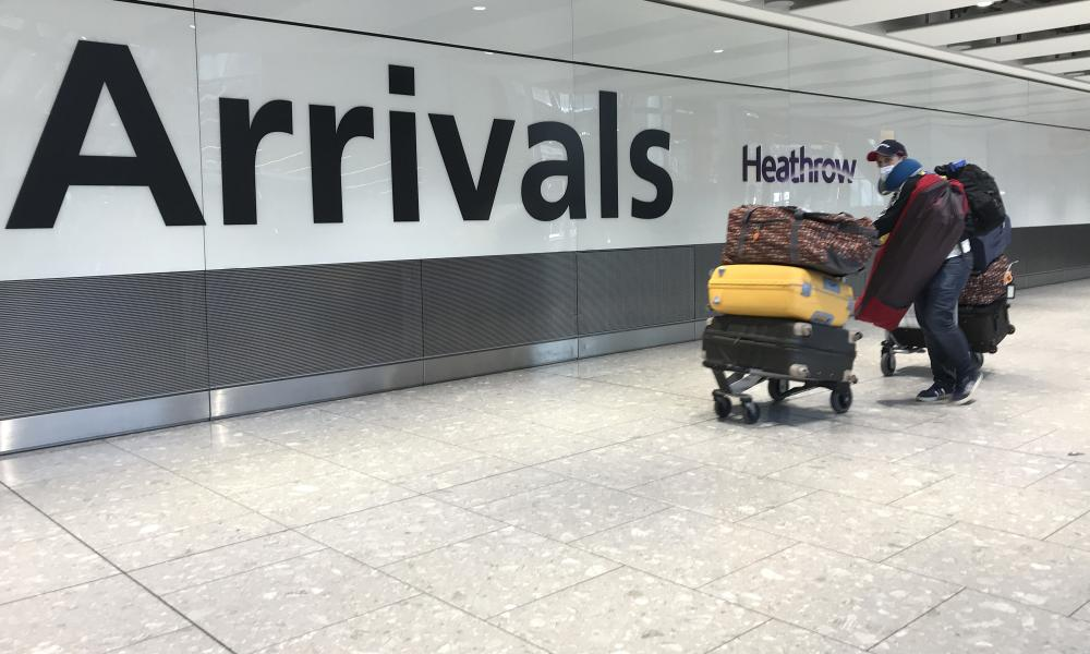 A passenger wears a mask as he arrives at Heathrow airport