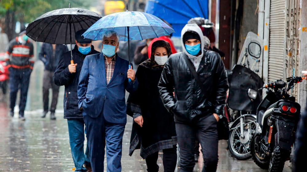 People walk in the rain past closed shops along a street in Iran's capital Tehran on Saturday.
