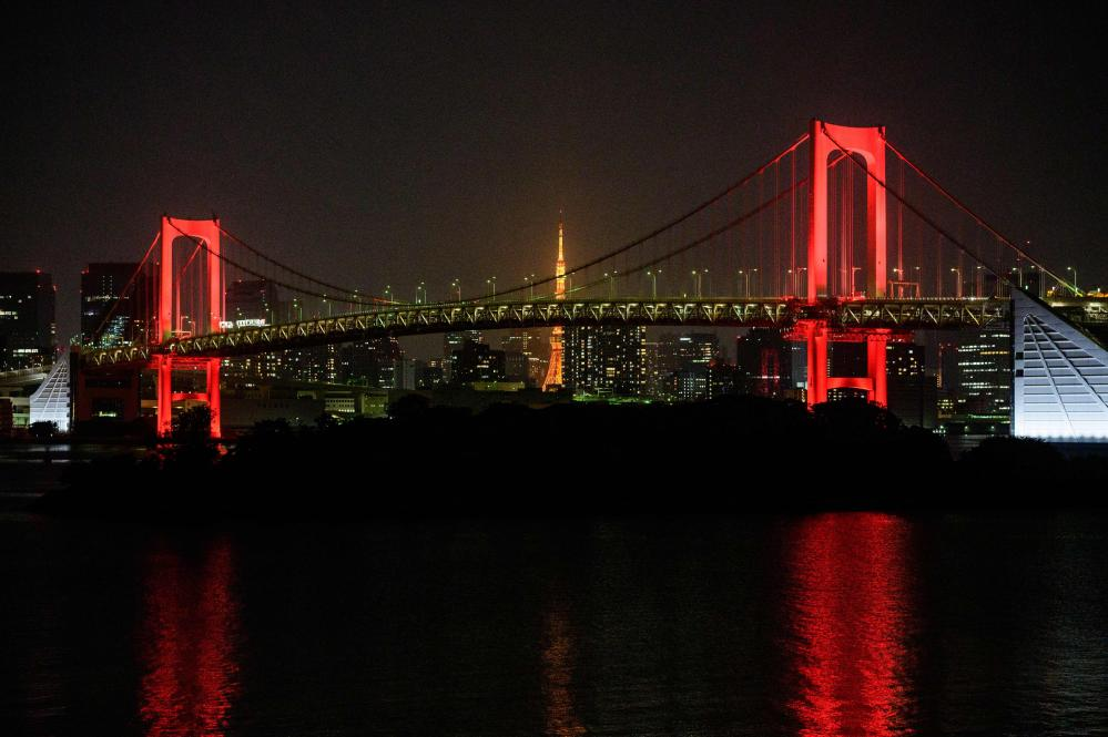 Tokyo's Rainbow bridge is lit in red after authorities issued an alert due to an increase coronavirus cases.