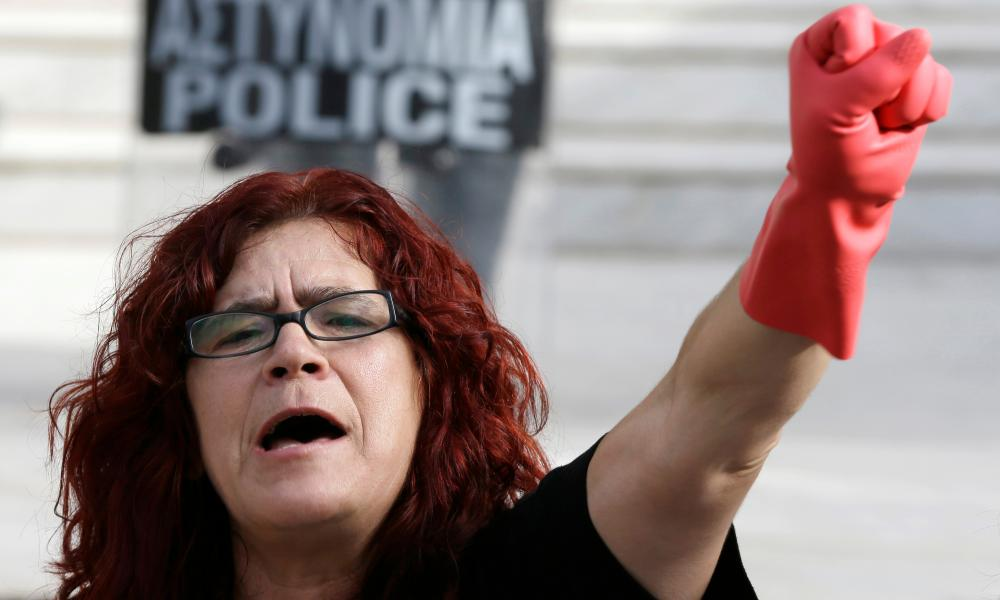 A cleaner puts her rubber gloves to work in a protest in Athens.