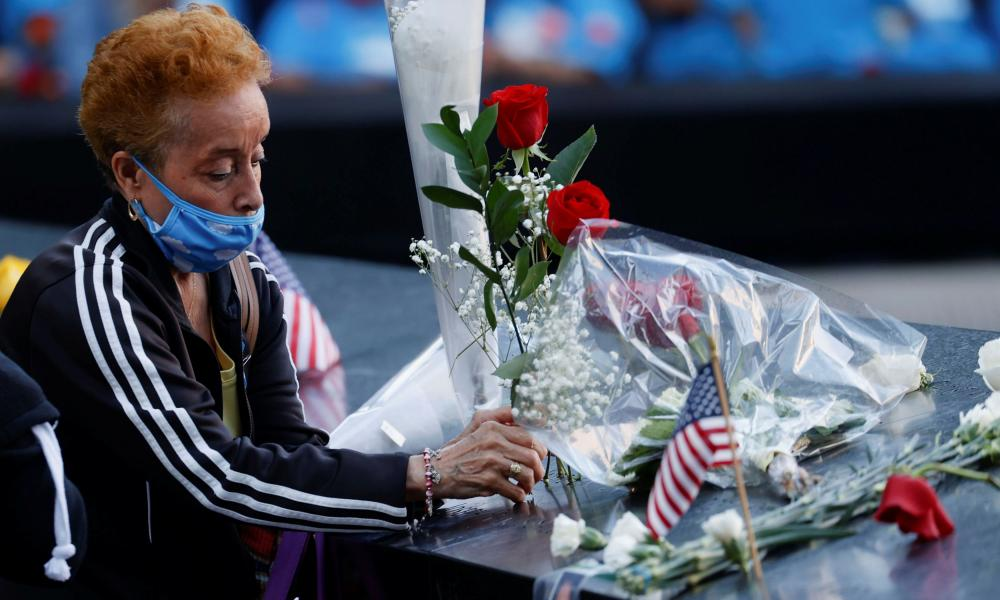 A woman places flowers as she visits the 9/11 Memorial on the 20th anniversary of the September 11 attacks in Manhattan, New York City.