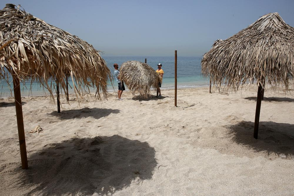 Workers place umbrellas on a beach near Athens, ahead of their reopening later this week.