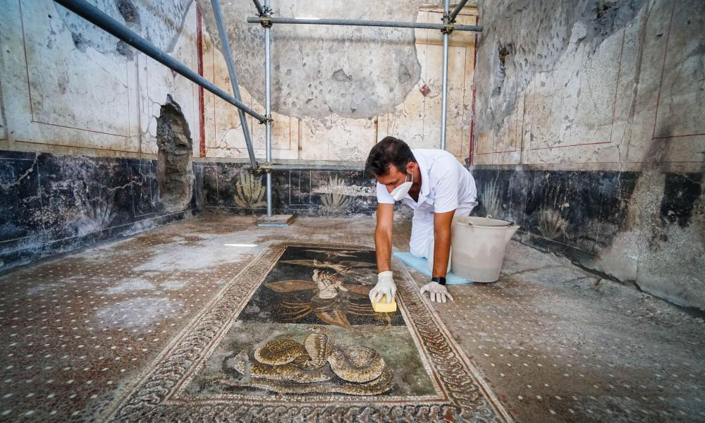 A worker cleans a mosaic at a nearby Casa di Orione, which will also be opening.