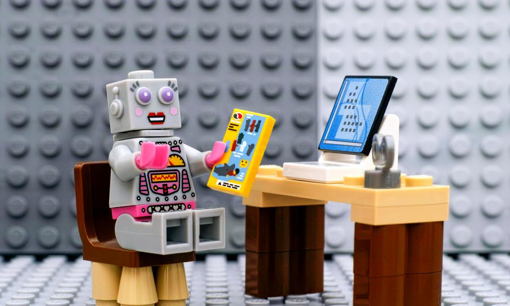 Lego robot minifigure with instruction sitting near computer
