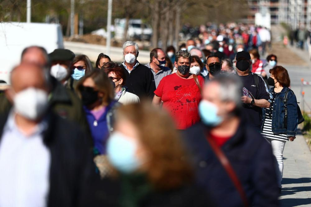 People wait in a queue before receiving their first dose of the AstraZeneca Covid-19 vaccine outside Enfermera Isabel Zendal hospital in Madrid, Spain, on 6 April, 2021.