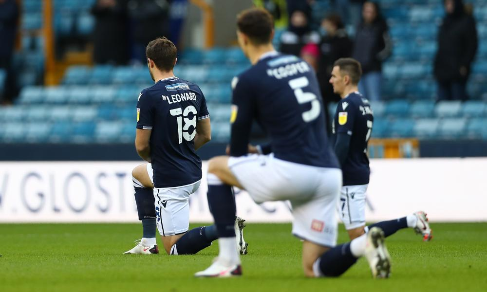 The Millwall players kneel before the match against Derby.