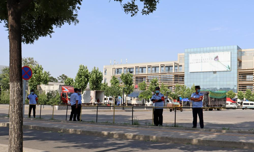 Security staff members patrol an entrance to the Xinfadi wholesale market, in Beijing, where a new coronavirus cluster has been reported.
