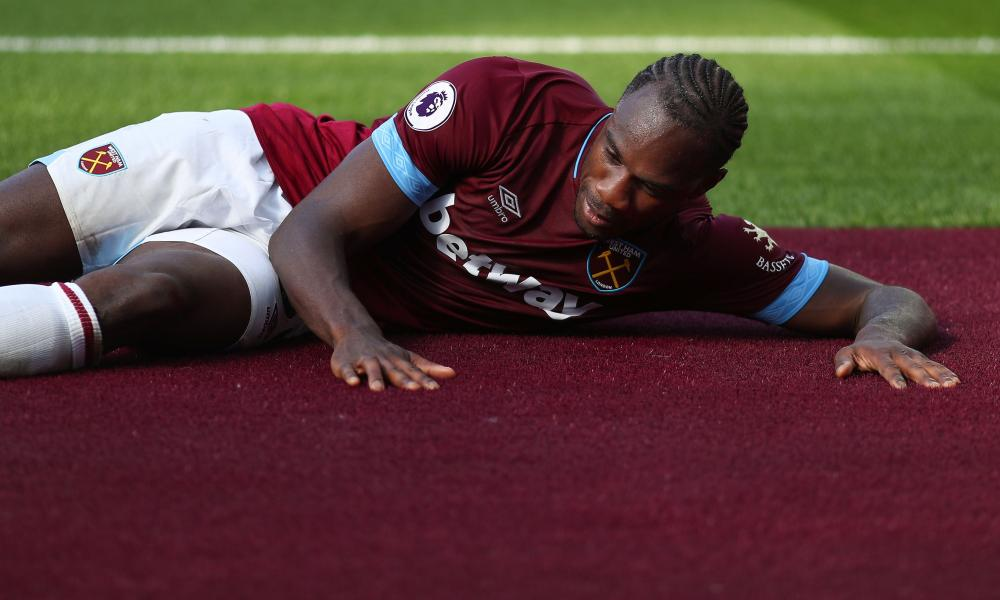 Michail Antonio of West Ham United rubs the new claret carpet that surrounds the pitch in celebration after scoring the opening goal.