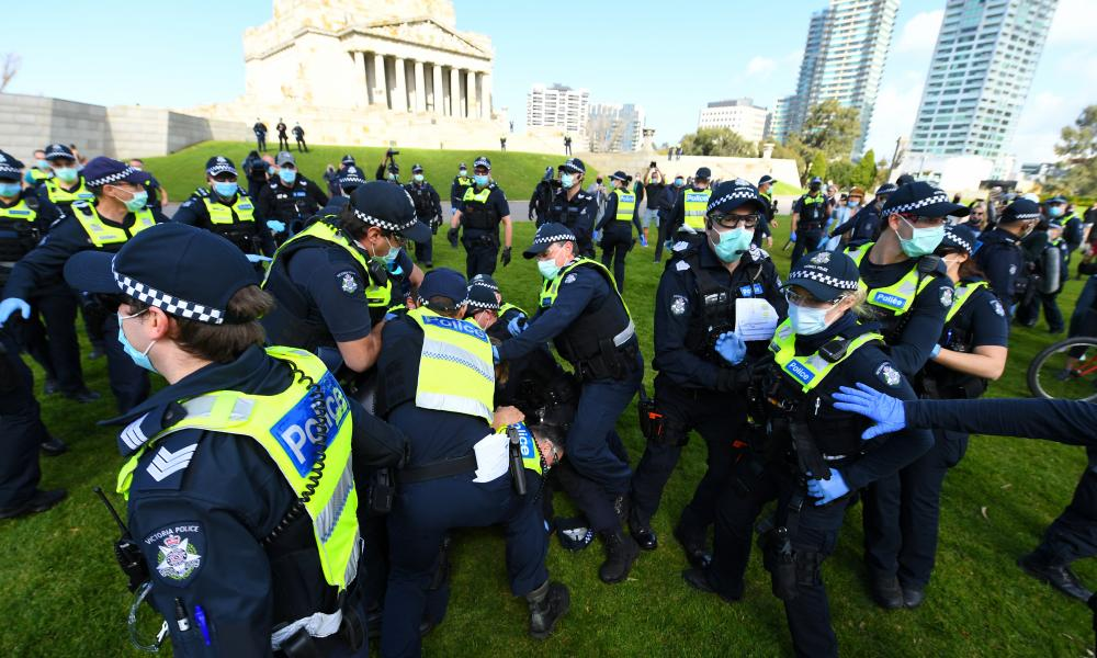 An anti-lockdown protester scuffles with with police outside the Shrine of Remembrance