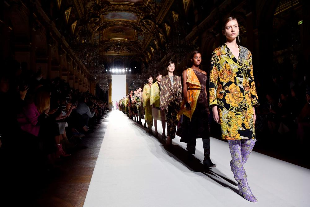Models in serious boots and cheerful dresses at Dries Van Noten.