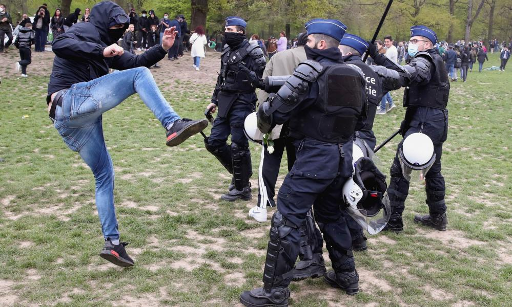 """Police officers scuffle with a man at the Bois de la Cambre/Ter Kamerenbos park as people gather for a party called """"La Boum 2"""" in defiance of Belgium's coronavirus measures on 1 May."""