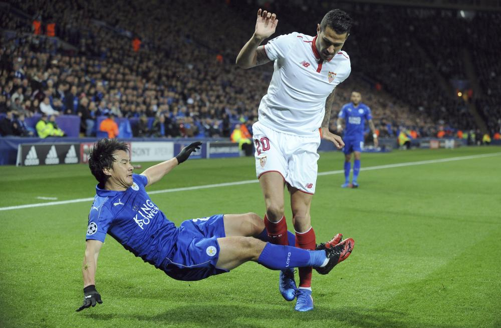 Leicester's Shinji Okazaki, left, and Sevilla's Vitolo tussle.