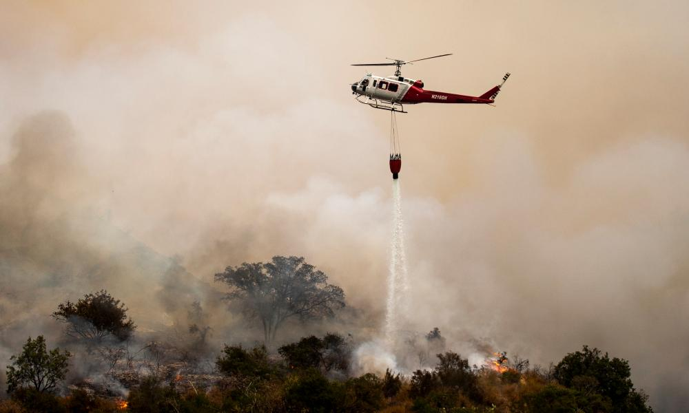 A helicopter makes drops water over the Bobcat fire, burning in the Angeles National Forest, near Arcadia, California.