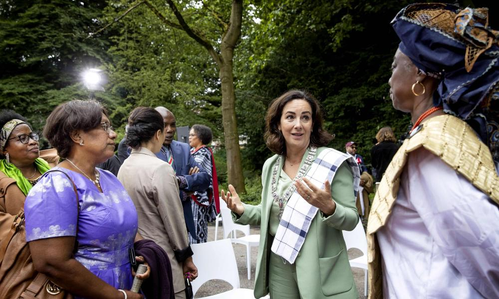 Three women, two black and one white, talking in a park