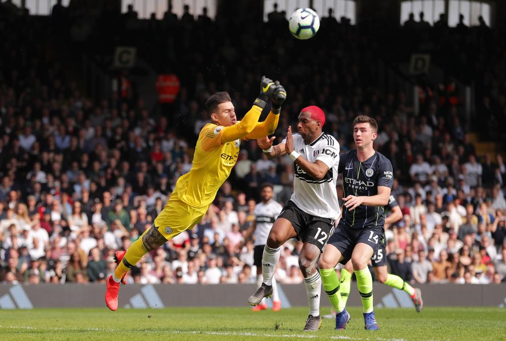 Ederson of Manchester City punches the ball away from Ryan Babel of Fulham.